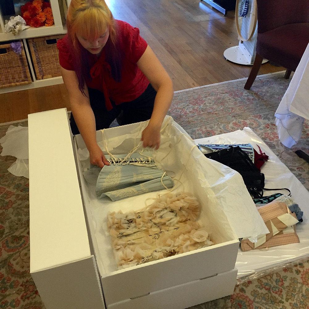 Textile conservator at work here packing some Sparkle Wren corsets