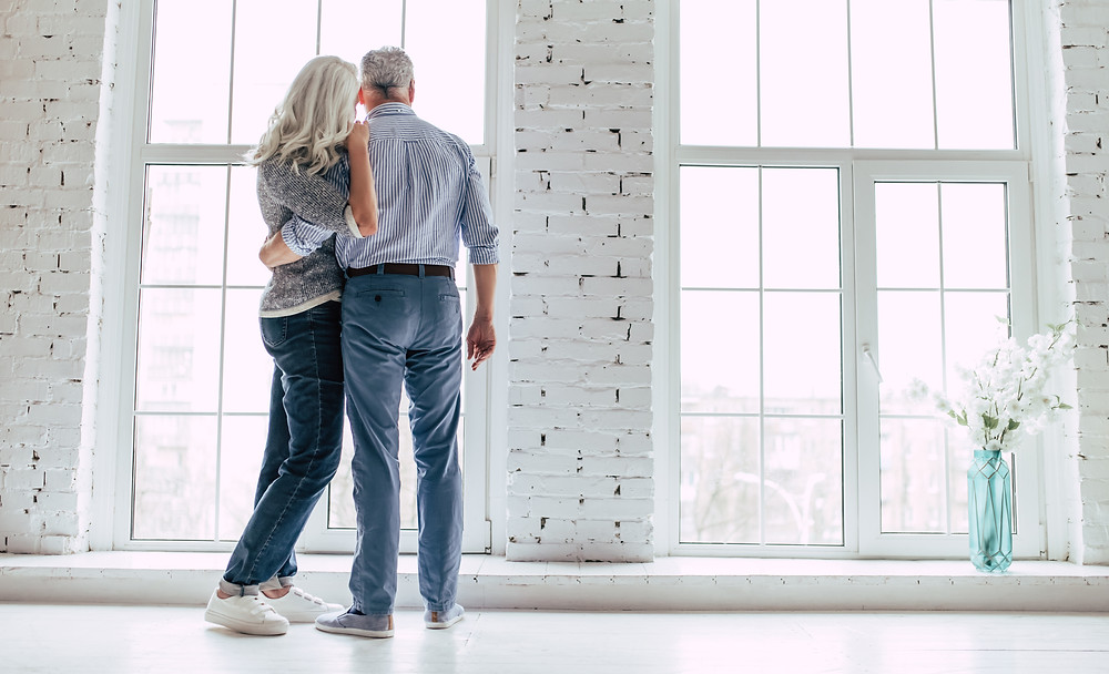 Older man and woman looking out large windows