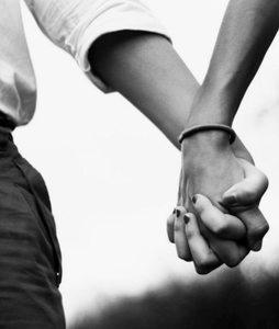 Greyscale closeup of man and woman holding hands