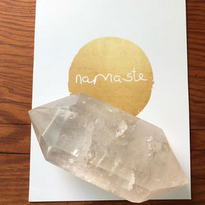 Large crystal stone on top of painted Namaste logo