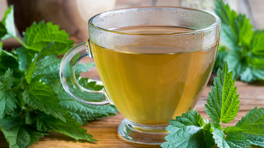 A%20cup%20of%20nettle%20tea%20on%20a%20wooden%20table%2C%20with%20fresh%20stinging%20nettles%20in%20