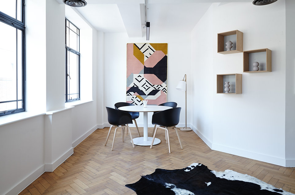 white loft style room, black windows, black plastic dining chairs with natural wood legs, white, modern table, gold floor lamp with goose neck and white shade, large, modern pink, black, white, grey and mustard yellow abstract painting, harringbone wood floor, black and white cow hide rug, square wall shelves, grey vases