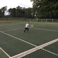 Playing tennis.