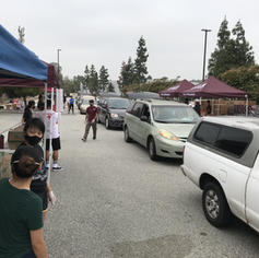 Cars driving through each station for volunteers to load foods into their trunks