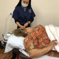Licensed acupuncturist providing treatment for a patient.