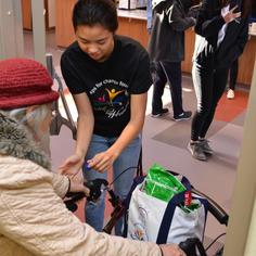 Volunteer helping an elderly out the door.