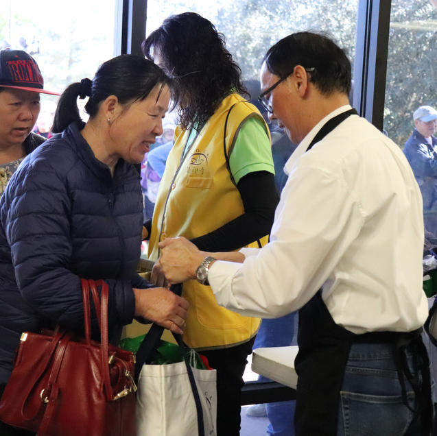 Volunteer handing off a tote bag to an individual.
