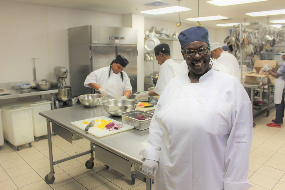 Photograph shows Deondre Holt smiling in the kitchen with students working behind her