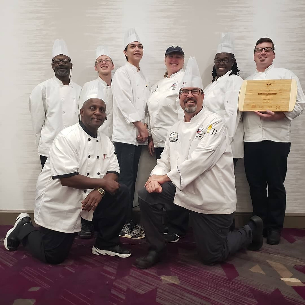 Graduates of the culinary training program stand together for a class photo