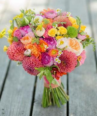 a summer mixed bridal bouquet of dahlias, ranunculas, spray roses, bluplurum, garden roses, zinnias, feaver few, dianthus, lisimachia and freesia weddings by Anderson Florist Tillamook Oregon