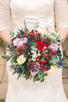 Winter bridal bouquet with red lavender blue and cream flowers weddings by Anderson Florist Tillamook Oregon