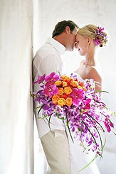 Beautiful purple orchids an orange spray roses make up this stunning cascading bridal bouquet in Pacific City Oregon
