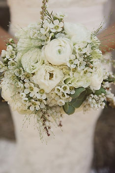All white bridal bouquet with ranunculas, waxflower, explosion grass and heather