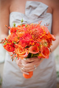 Coral and orange bridal bouquet with calla lilies, roses, protea, ranunculas, and crowcosmia Tilllamook oregon weddings by anderson florist oregon coast florist