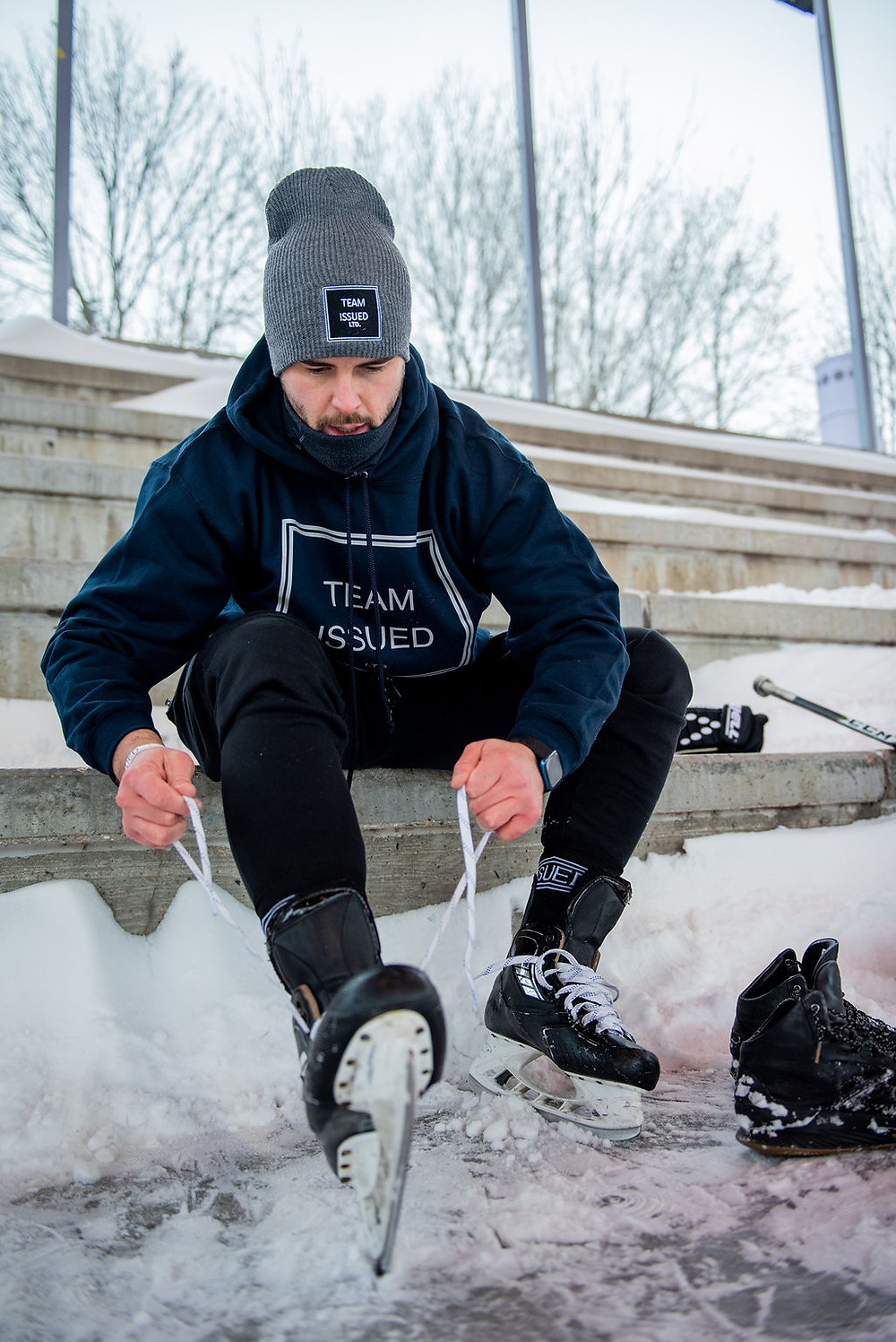 Man in his 20's on a park bench lacing up black hockey skates wearing a Team Issued outfit including a blue hoody, black sweatpants, and a grey toque