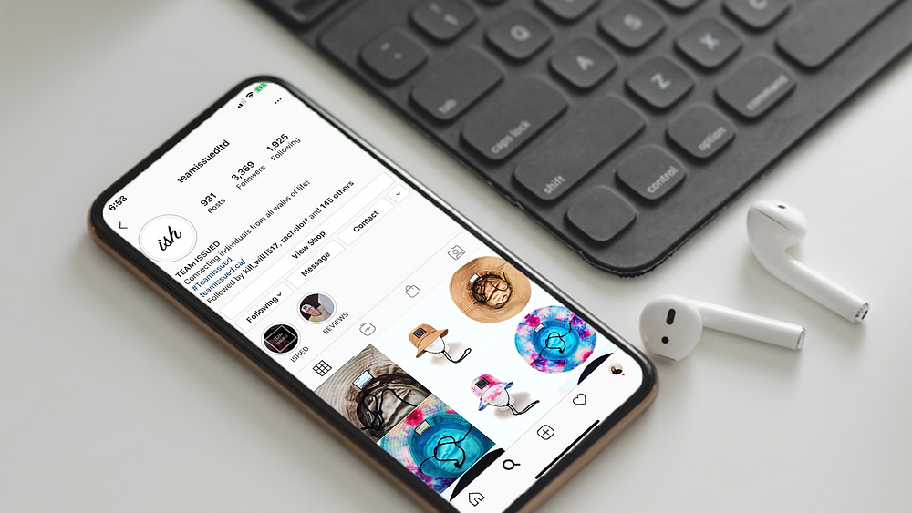 Black iPhone open to the Team Issued Ltd Instagram page on a white desk beside a black keyboard and white air pods