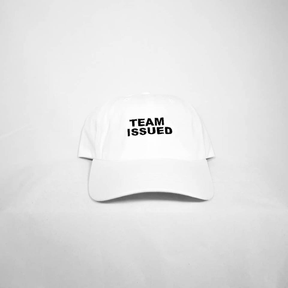 """White """"dad hat"""" with black Team Issued logo in front of white background"""
