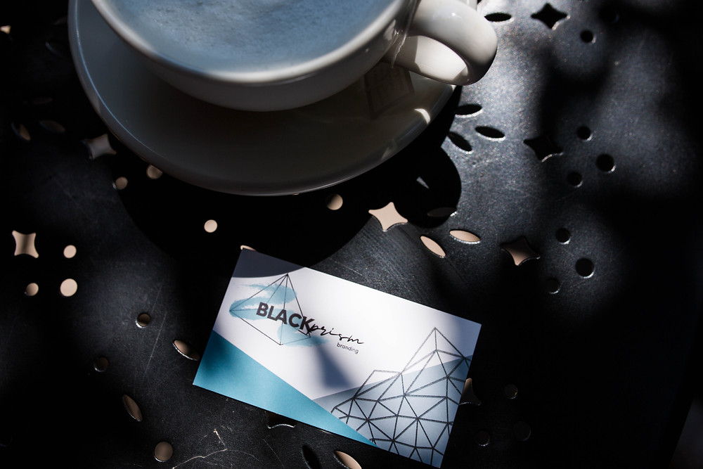 A Black Prism Branding business card that is white, with the Black Prism logo along with blue and silver prisms and triangles. The card is on a black metal table and there is a white coffee cup and saucer nearby.