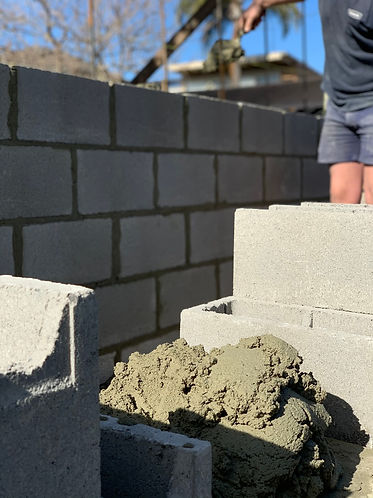 Photo is of a bricklayer laying a block
