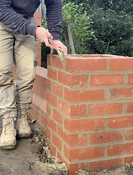 A bricklayer in Hobart laying a red brick fence in Hobart