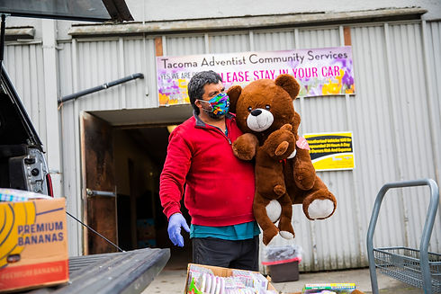Volunteer Carrying Large Teddy-bear to Client