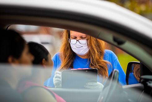 Volunteer verifying paperwork for client in vehicle