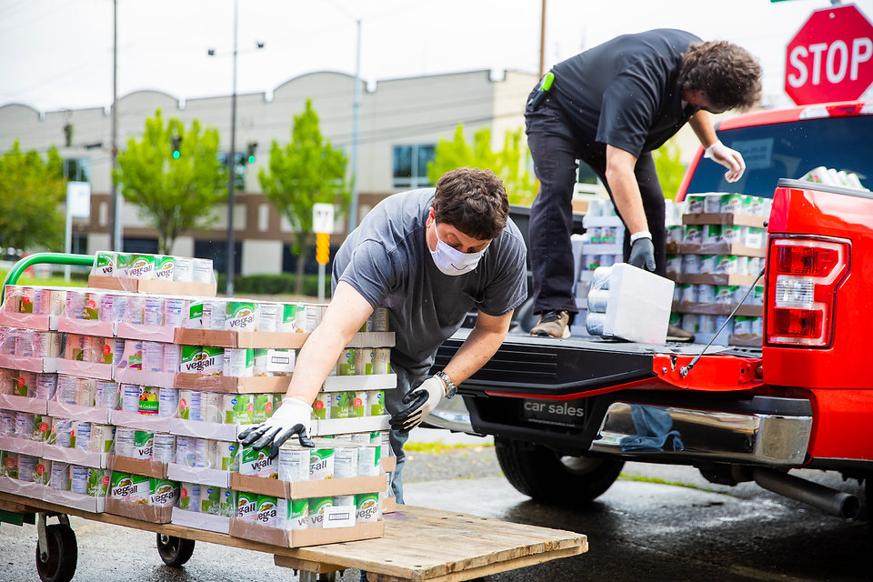 Two volunteers unloading canned goods onto pallet from delivery truck