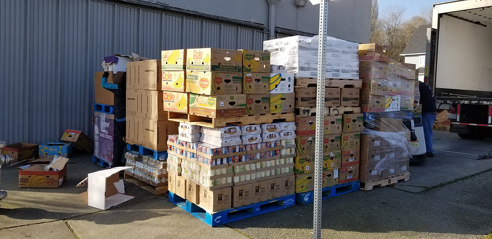 Pallets with towers of cardboard boxes holding various food items