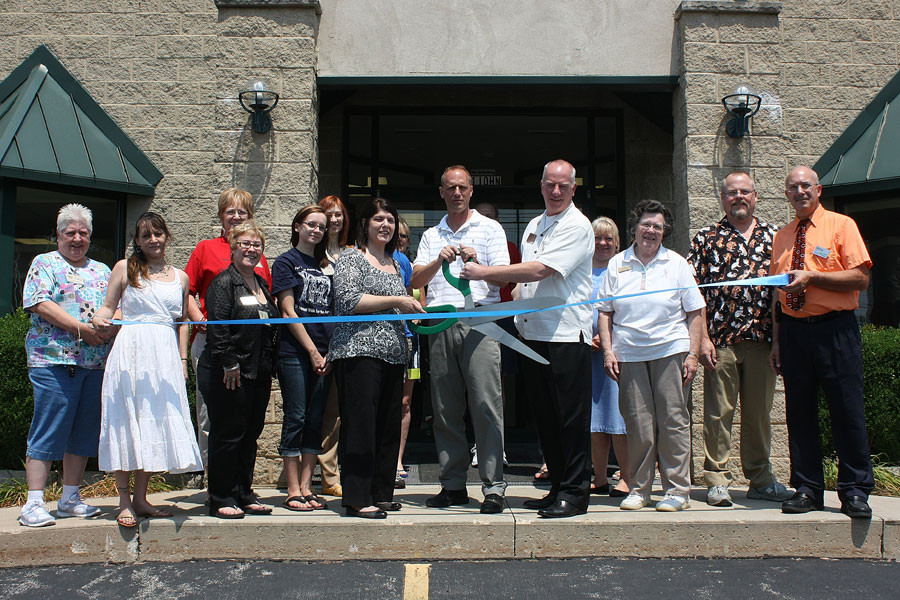 The director, volunteers, board of directors and community members cutting the ribbon on opening day
