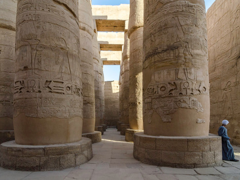 An Egyptian man in robes leans against temple pillar