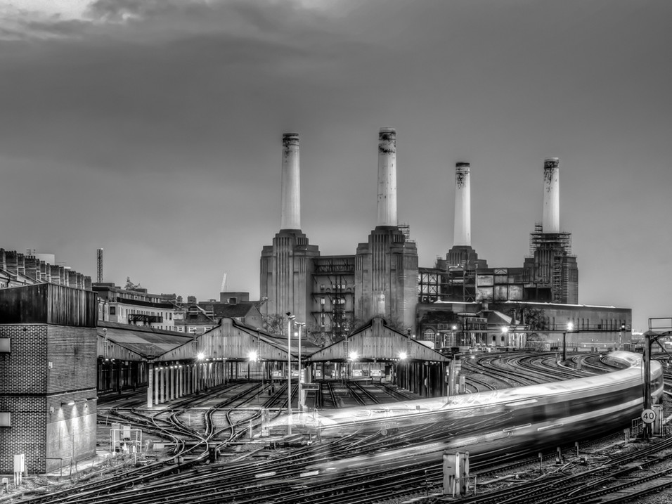 Trains pass Battersea Power Station.