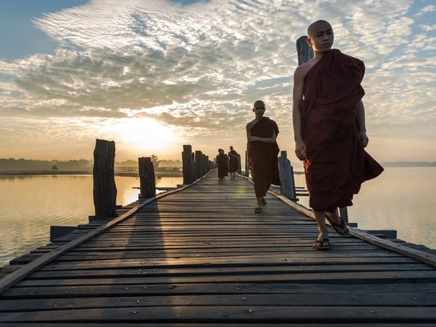Monks walking along U-bein Bridge at dawn