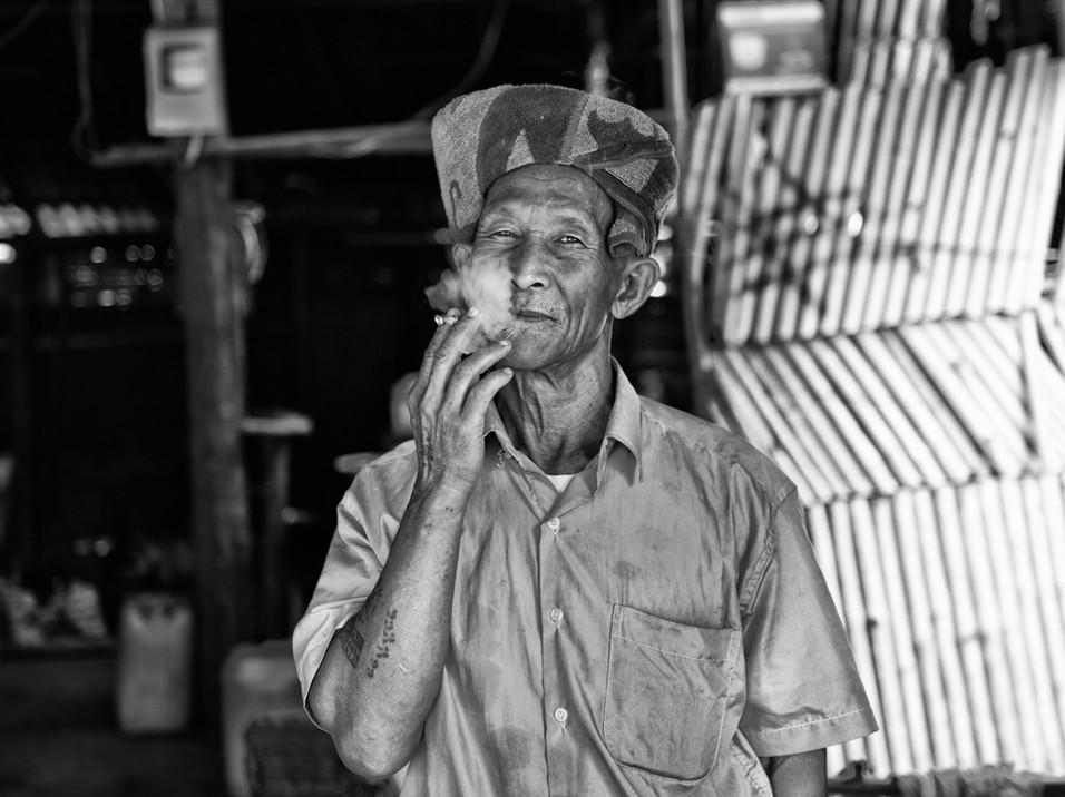 A Burmese man smokes a hand-rolled cigar