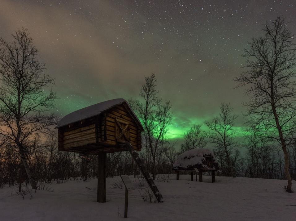Aurora over a winter food storage cabin