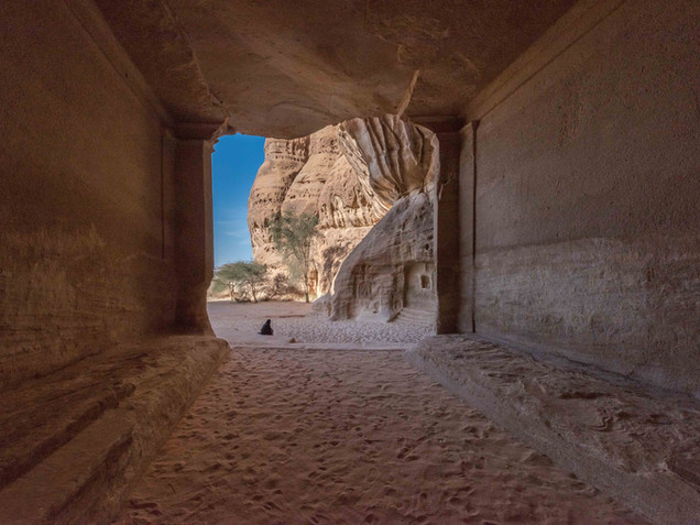 A Saudi woman sits outside a huge sandstone tomb
