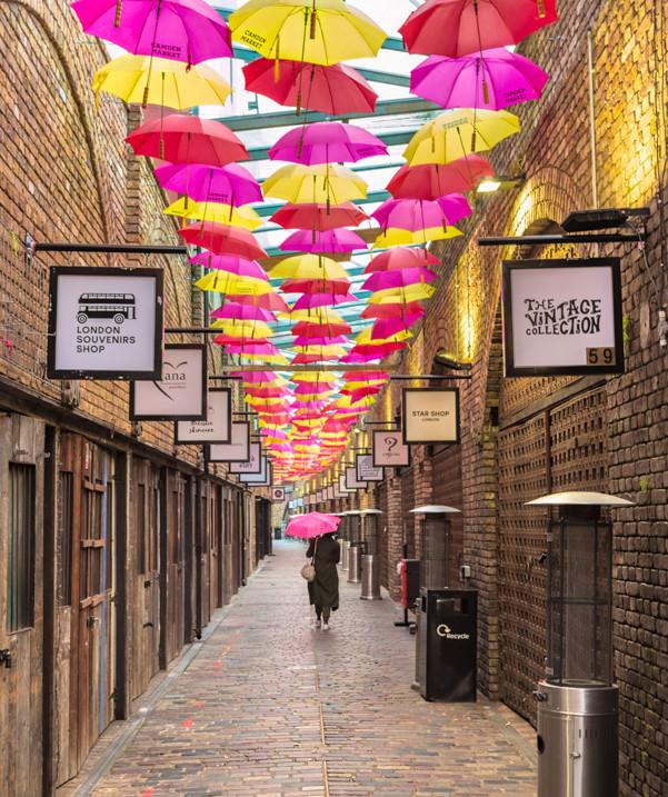 A woman walks under a ceiling of umbrellas, Camden Market