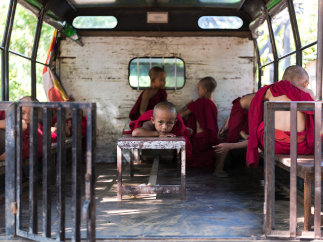 Monks resting in the back of a school bu