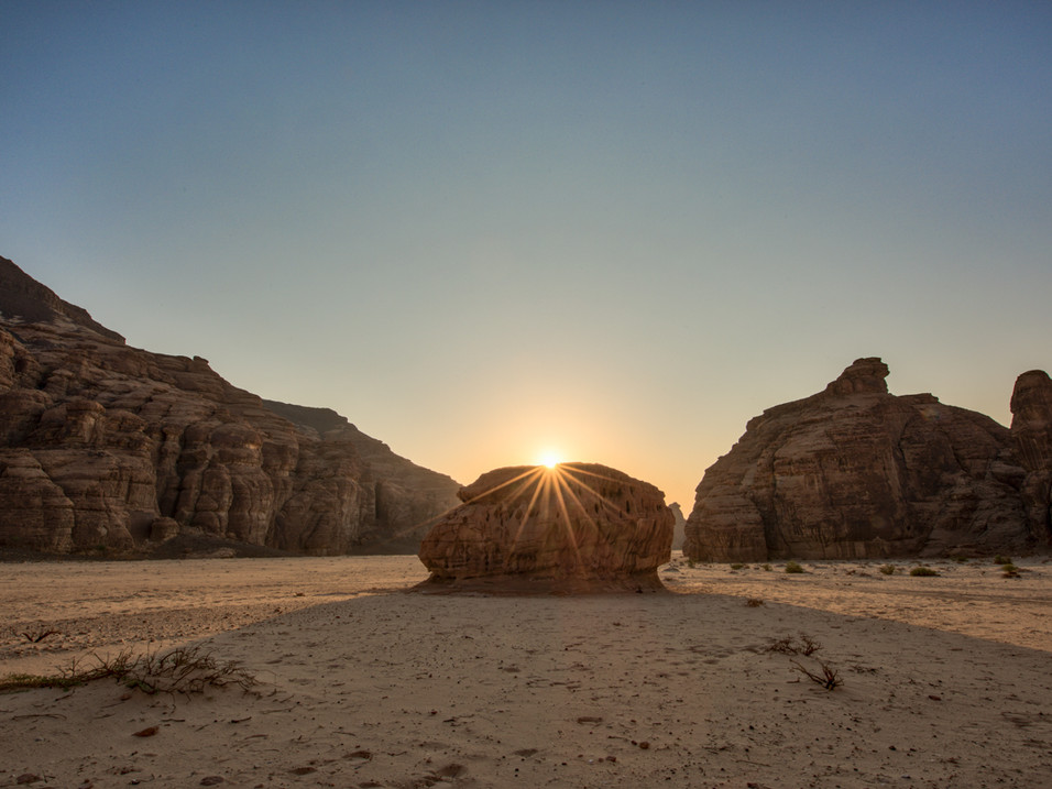 The sun rises behind a monolith in AlUla