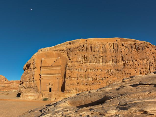 The moon rises over tombs in Hegra, Saudi Arabia