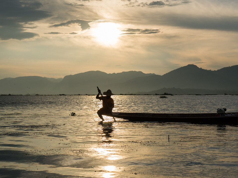 A fisherman on Inle Lake searches for fish
