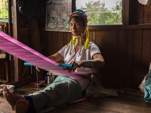 A long-neck woman of Inle Lake weaves cl