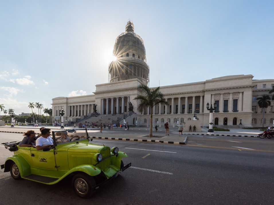 A jeep drives past the National Capitol Building, Havana