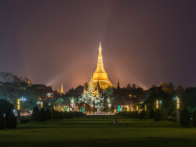 A couple sit in front of Shwedagon Pagoda, Yangon