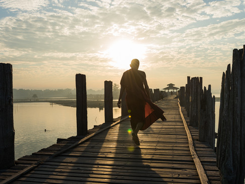 The sun illuminates a monk's robes on U-bien Bridge, Mandalay