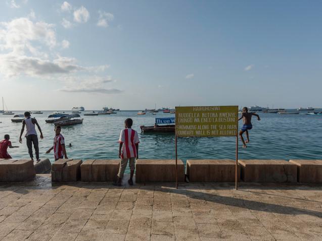 Young boys jumping off the sea wall in Zanzibar
