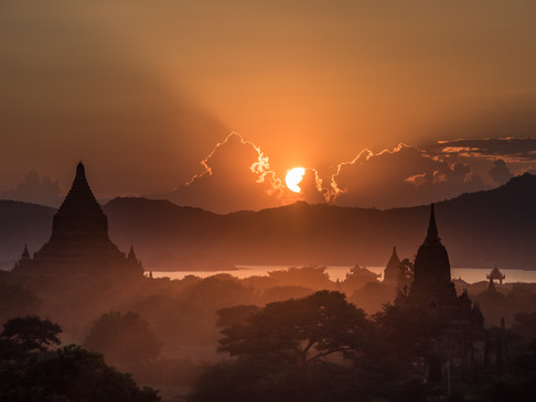 The sun sets behind temples in Bagan