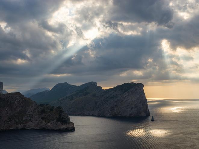 A boat sails round the Majorca coastline