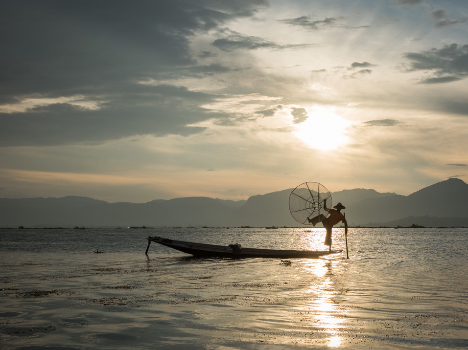 A fisherman on Inle Lake poses with his fishing net