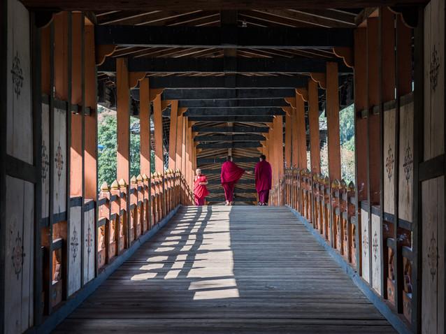 Monks cross a bridge in Bhutan.jpg