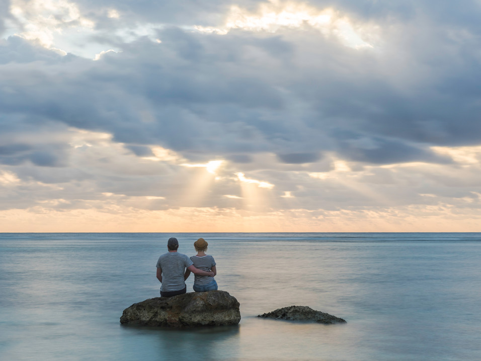 A couple watch the sunset in the Cayman Islands